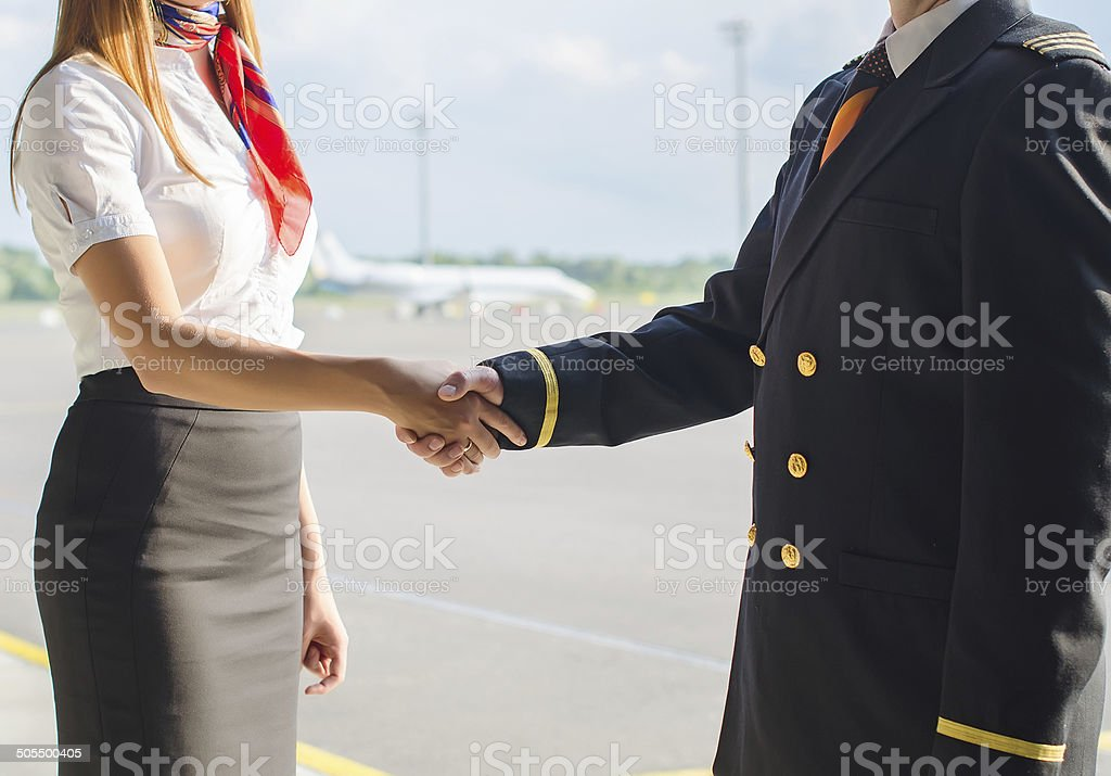 Pilot and stewardess shaking hands on airfield background. stock photo