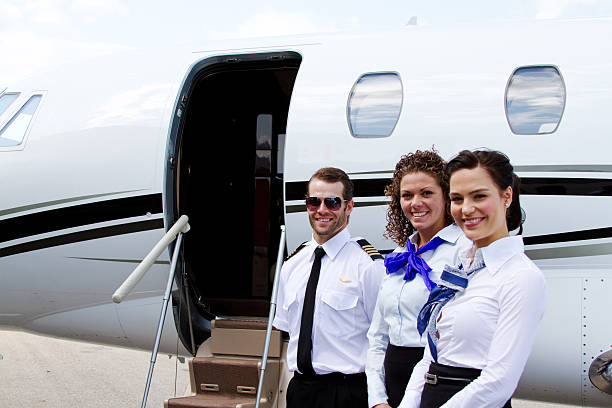 Pilot and stewardesses by plane stock photo