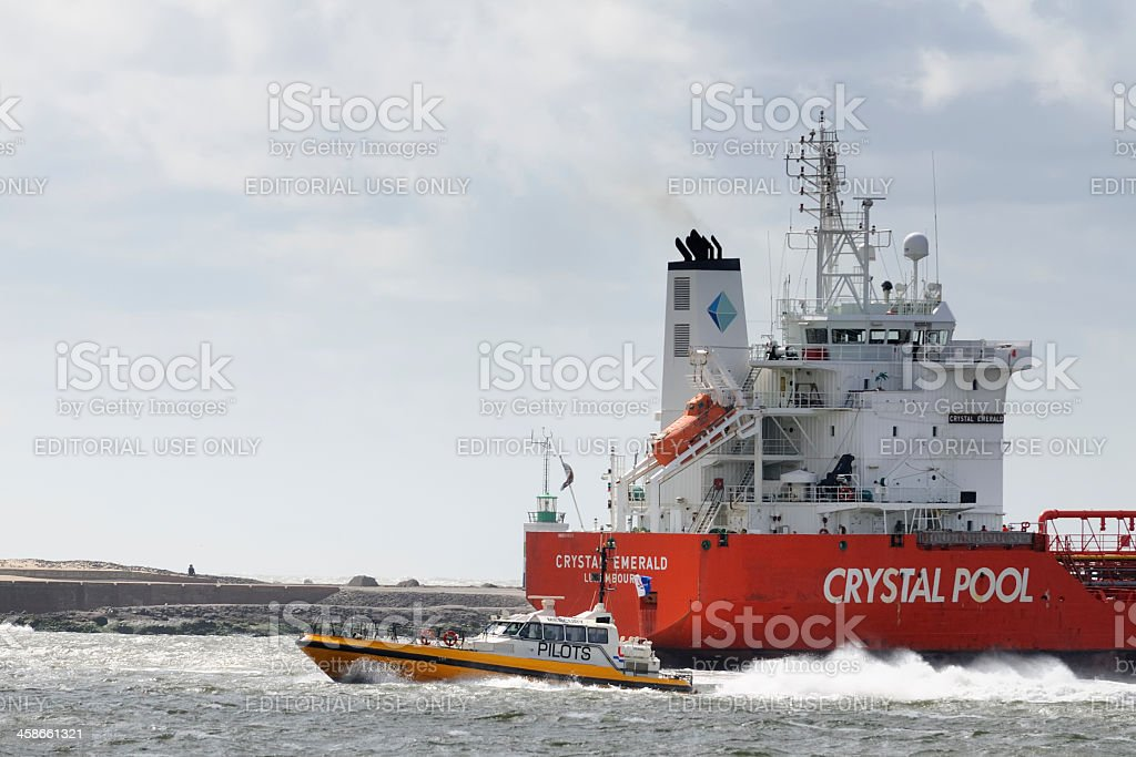 Pilot boat and cargo ship royalty-free stock photo