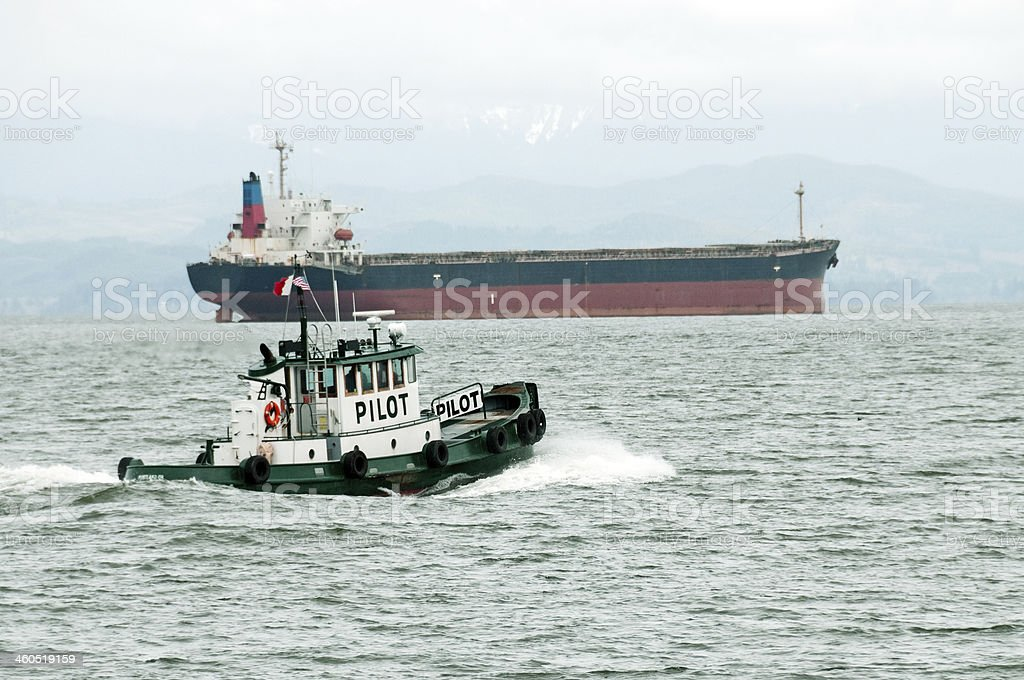 Pilot boat and freighter in Columbia River at Astoria OR royalty-free stock photo