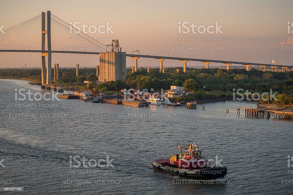Pilot boat cruises at dusk on Savannah River in Savannah, GA. stock photo