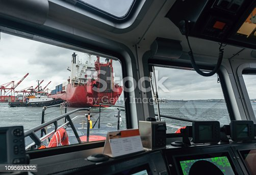 A view form the helm of a pilot boat while following a container ship.