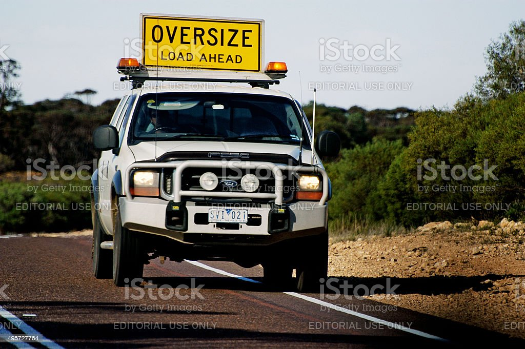 Pilot car before a huge Australian truck stock photo