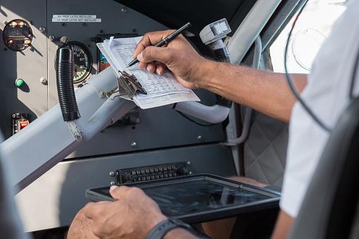 Pilot Checking Checklist in Airplane Cockpit
