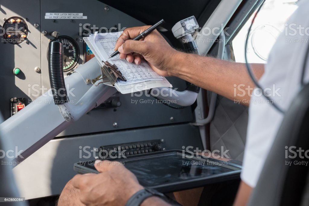Pilot Checking Checklist in Airplane Cockpit stock photo