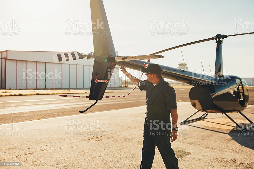 Pilot checking helicopter tail during preflight check stock photo