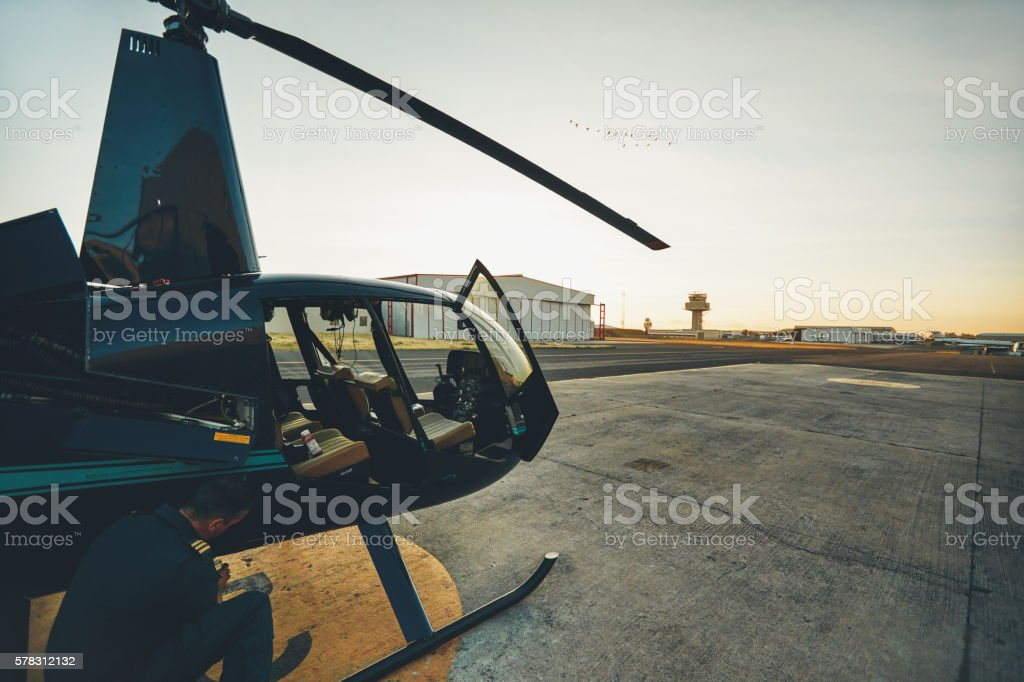 Pilot doing pre flight inspection at helicopter stock photo