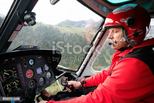 A male helicopter pilot adjusts flight controls while navigating in the Swiss Alps. Wide angle in-flight image includes flight controls and instruments. The helicopter is used for mountain rescue as well as general transportation in the mountainous Bernese Oberland region.