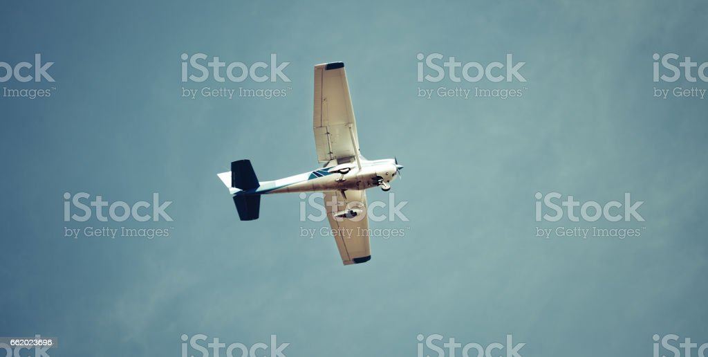 Pilot flying recreational airplane mid air flying in sky royalty-free stock photo
