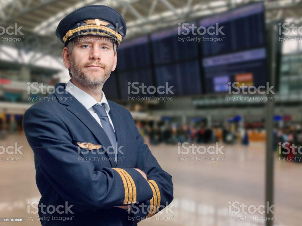 Pilote en uniforme der mit goldenen Streifen und Kappe kreuzte seine Arme beim Stehen im Flughafen - Photo