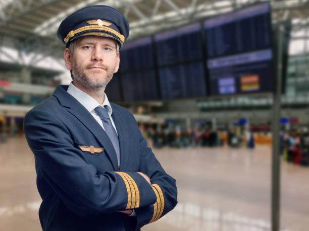 Pilot in der Uniform mit goldenen Streifen und Kappe kreuzte seine Arme beim Stehen im Flughafen stock photo