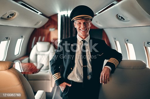 Experienced pilot in uniform standing in cabin of private jet. Pilot in command inside the aircraft.