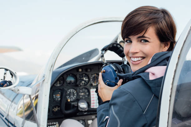 Pilot in the aircraft cockpit Smiling female pilot in the light aircraft cockpit, she is holding aviator headset and looking at camera military private stock pictures, royalty-free photos & images