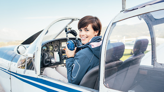 Smiling female pilot in the light aircraft cockpit, she is holding aviator headset and checking controls