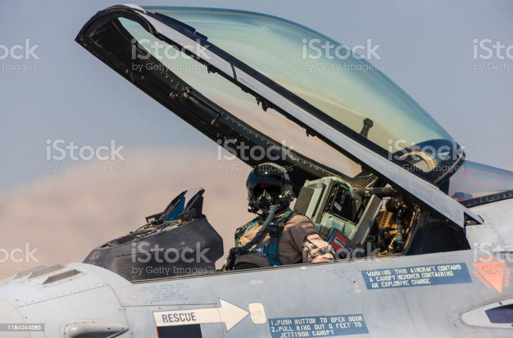 Pilot in the cocpit of an F-16 fighter jet plane. Pilot in the cocpit of an F-16 fighter jet plane. Adult Stock Photo