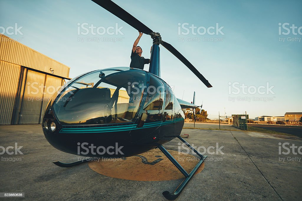 Pilot inspecting the rotor blades of a helicopter stock photo