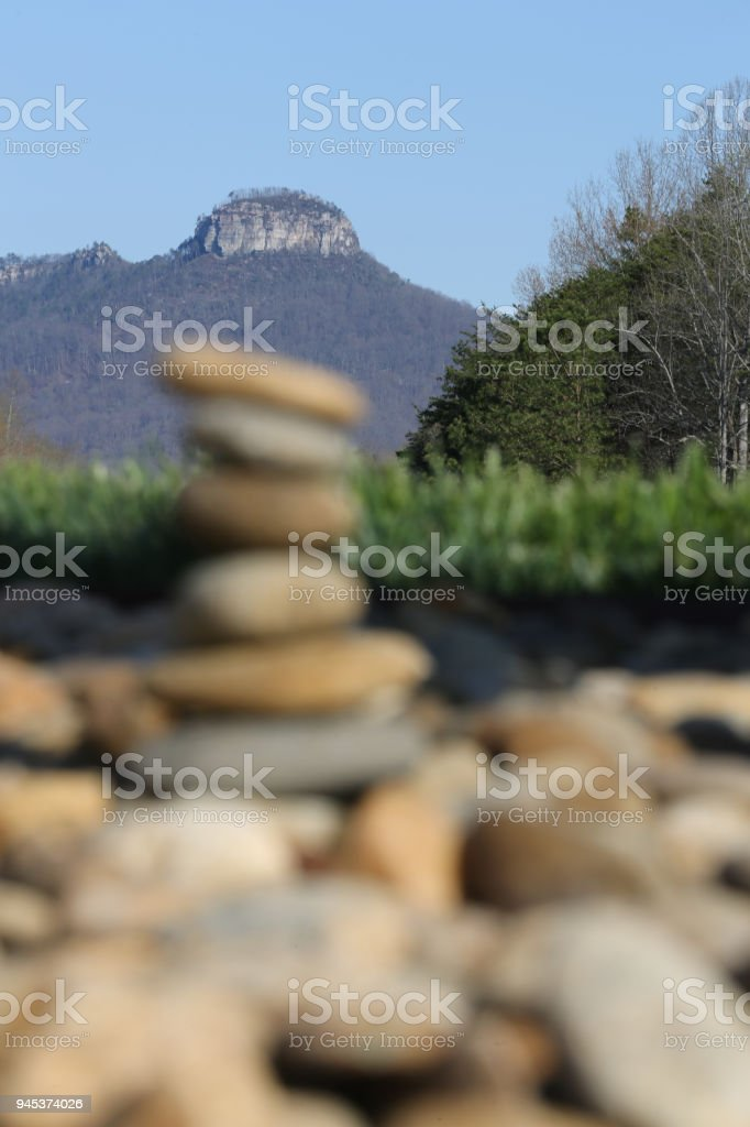 Pilot Mountain with pile of rocks in the foreground stock photo