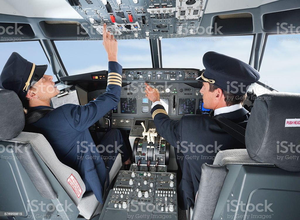 Pilot pushing button in airplane cockpit with co-pilot stock photo