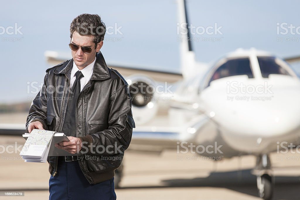 Pilot Reviewing Flight Map Outside Corporate Jet royalty-free stock photo