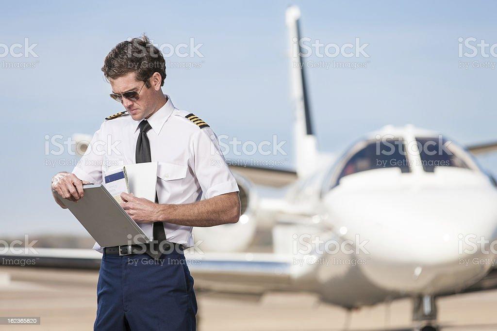 Pilot Reviewing Log Book Near Corporate Jet stock photo
