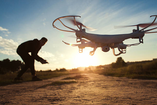 pilot running drone at sunset light, free space - drones stock photos and pictures