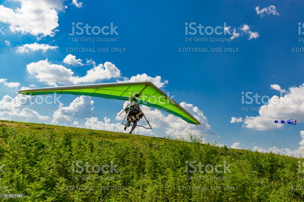 Pilot runs with a hang glider on a green grassy slope with blue sky and clouds above stock photo