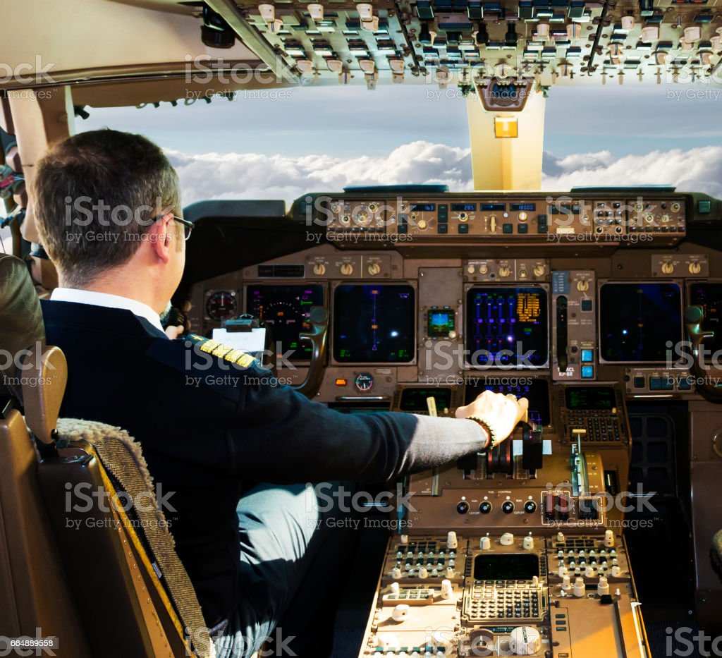 Pilot sitting in airplane cockpit stock photo