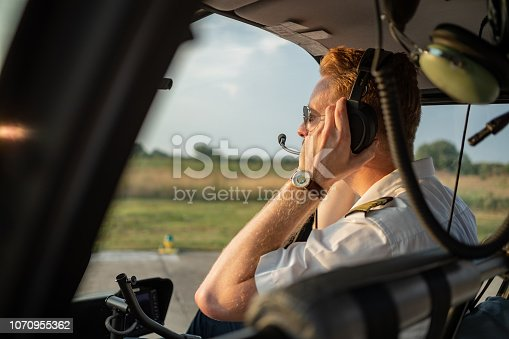 Redhead chopper pilot sitting in cockpit and adjusting headset