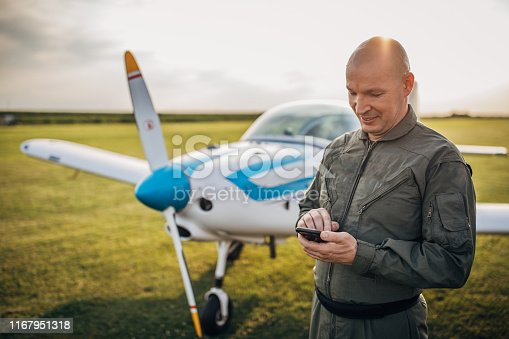 Pilot in uniform standing by the propeller airplane and using phone