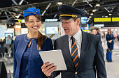 Happy pilot talking to a flight attendant and showing her something on a tablet computer – travel concepts