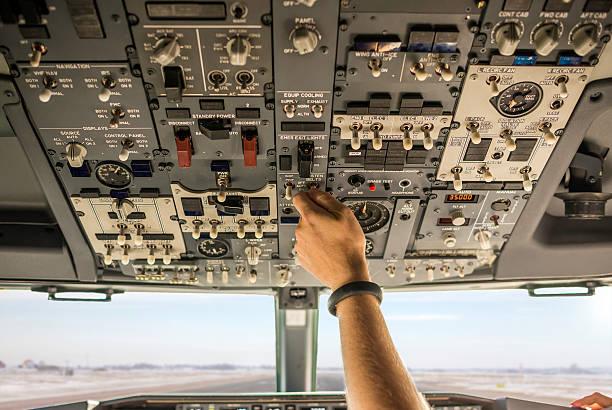 Pilot turning on fasten seat belts sign stock photo
