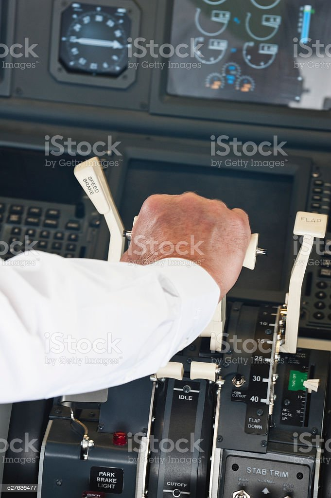 Pilot turning switching thrust lever in airplane cockpit stock photo