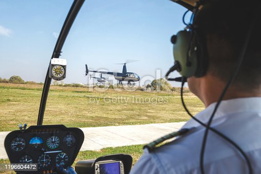 Pilot sitting in helicopter and watching two helicopters landing on airfield