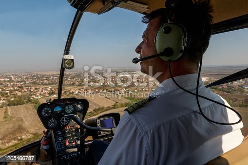 Pilot with headphones flying over residential district and fields in the plain area
