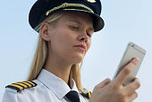 A blonde female pilot checking her phone on the way to work.