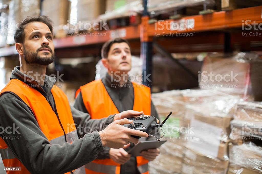 Piloting a Drone inside a warehouse. stock photo