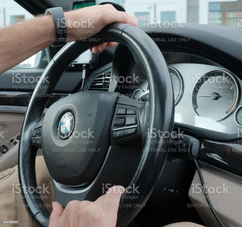 Pilot's hand on BMW steering wheel Mannheim, Germany - August 21, 2017: Pilot's hand on BMW steering wheel. BMW Motorrad is the motorcycle brand of the German company BMW, part of its Corporate and Brand Development division Automobile Industry Stock Photo