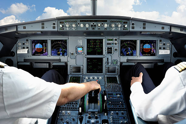 pilots in cockpit of modern jet aircraft - cockpit stock photos and pictures