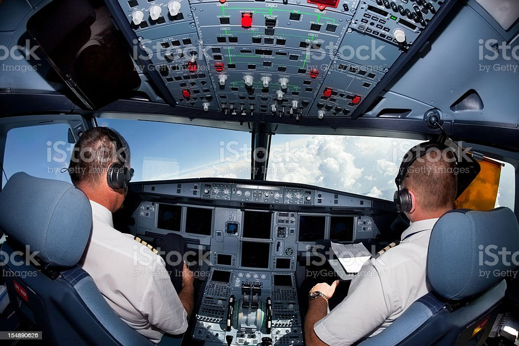 Pilots in the cockpit of commercial airplane royalty-free stock photo