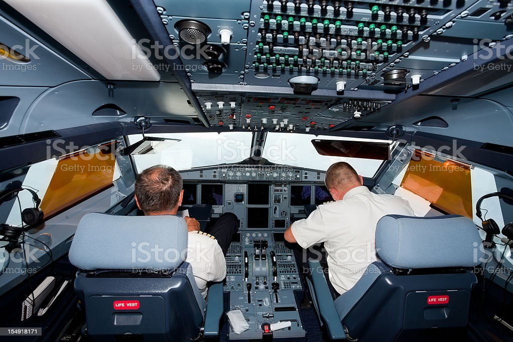 Pilots in the cockpit of commercial airplane Pilots in the cockpit of commercial airplane Air Vehicle Stock Photo