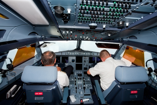 Pilots In The Cockpit Of Commercial Airplane Stock Photo - Download Image Now