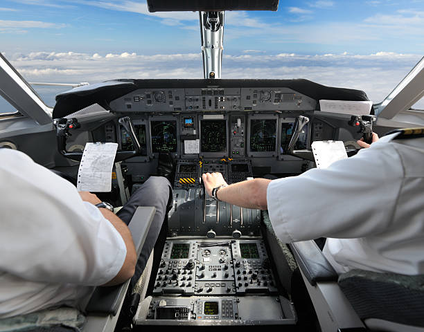 pilots in the cockpit - preparing for landing - pilot stock photos and pictures