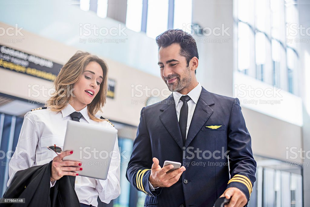 Pilots using digital tablet on the way to the plane stock photo