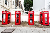 London, UK - September 12, 2018: Pimlico or Victoria in Westminster with typical architecture street road and front of four vibrant red telephone booth box during day