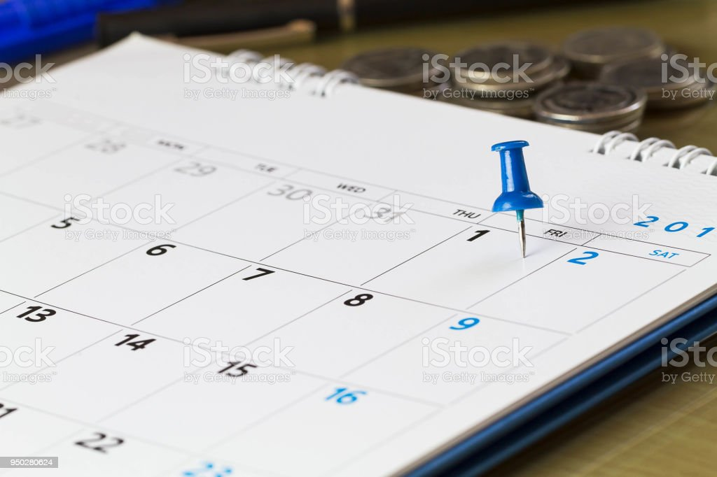 Pin on calendar on 1st of the month with blurred coins background, business concept stock photo