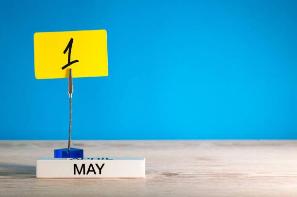 Broche sur le nombre de date du calendrier - le 1er mai. 1 jour du mois. Lieu de travail à fond bleu avec l'espace de la copie. Temps de printemps. Fête du travail - Photo