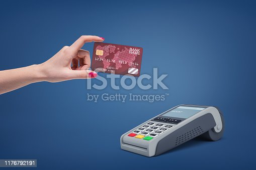 945598452istockphoto Pin pad and female hand holding plastic card on blue background 1176792191