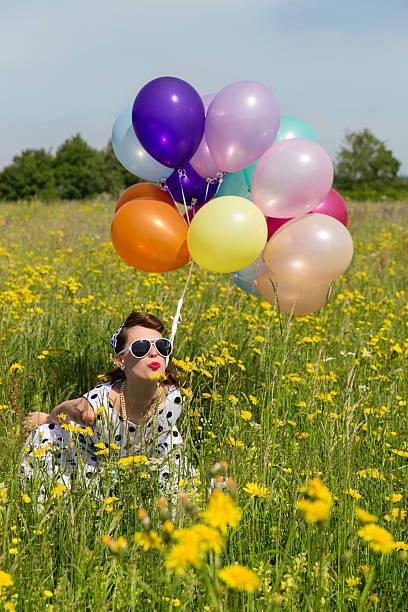 pin-up-mädchen auf einer wiese blumen mit bunten luftballons - rock n roll kleider stock-fotos und bilder