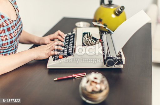 471445335istockphoto Pin Up girl with typewriter 641377322