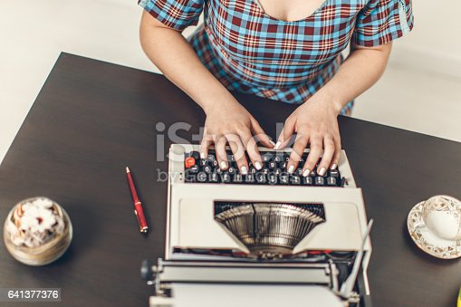 471445335istockphoto Pin Up girl with typewriter 641377376